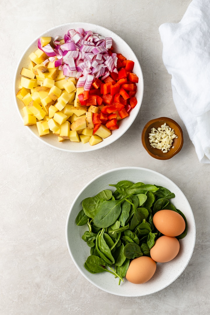 Bowls of chopped Yukon gold potatoes, red peppers, red onion, baby spinach, and eggs.