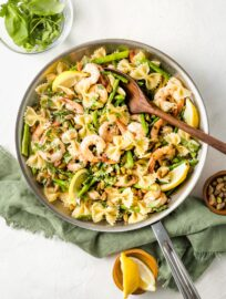 Skillet with lemon asparagus pasta with shrimp and pistachios.