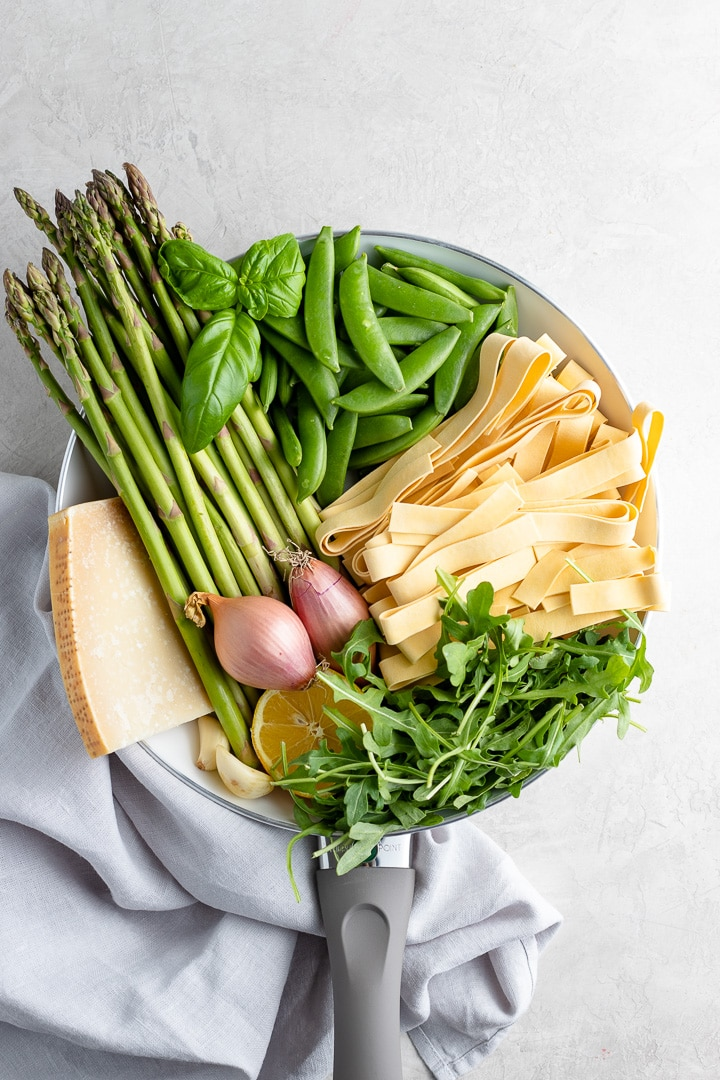Ingredients for making a creamy pasta Primavera - asparagus, fresh basil, pappardelle noodles, peas, arugula, shallots, garlic, Parmesan cheese.