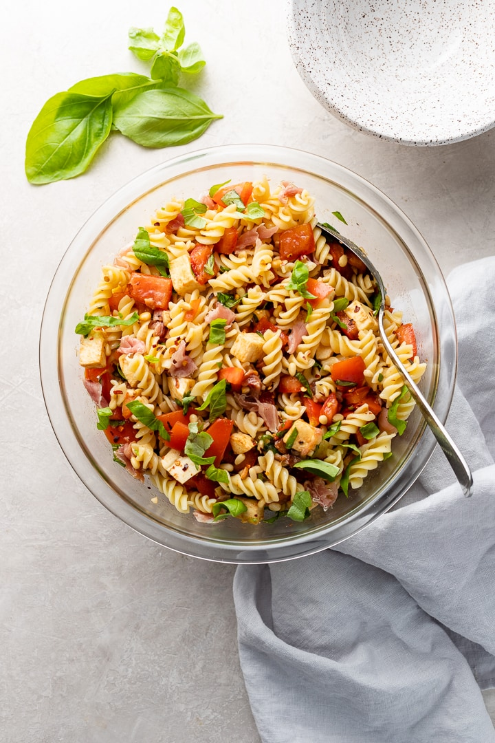 Large clear Pyrex bowl filled with a Caprese Pasta Salad including rotini, tomatoes, mozzarella, basil, prosciutto, pine nuts, and dressing.