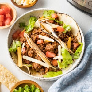Plate with ground beef tacos and Instant Pot in the background.