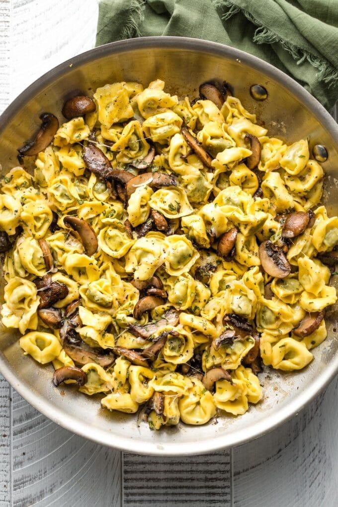 Skillet full of tortellini with mushrooms.
