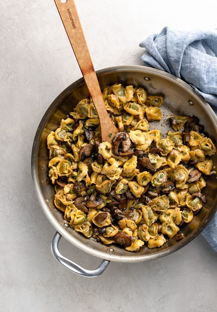 Skillet filled with cooked tortellini with mushrooms and Parmesan.