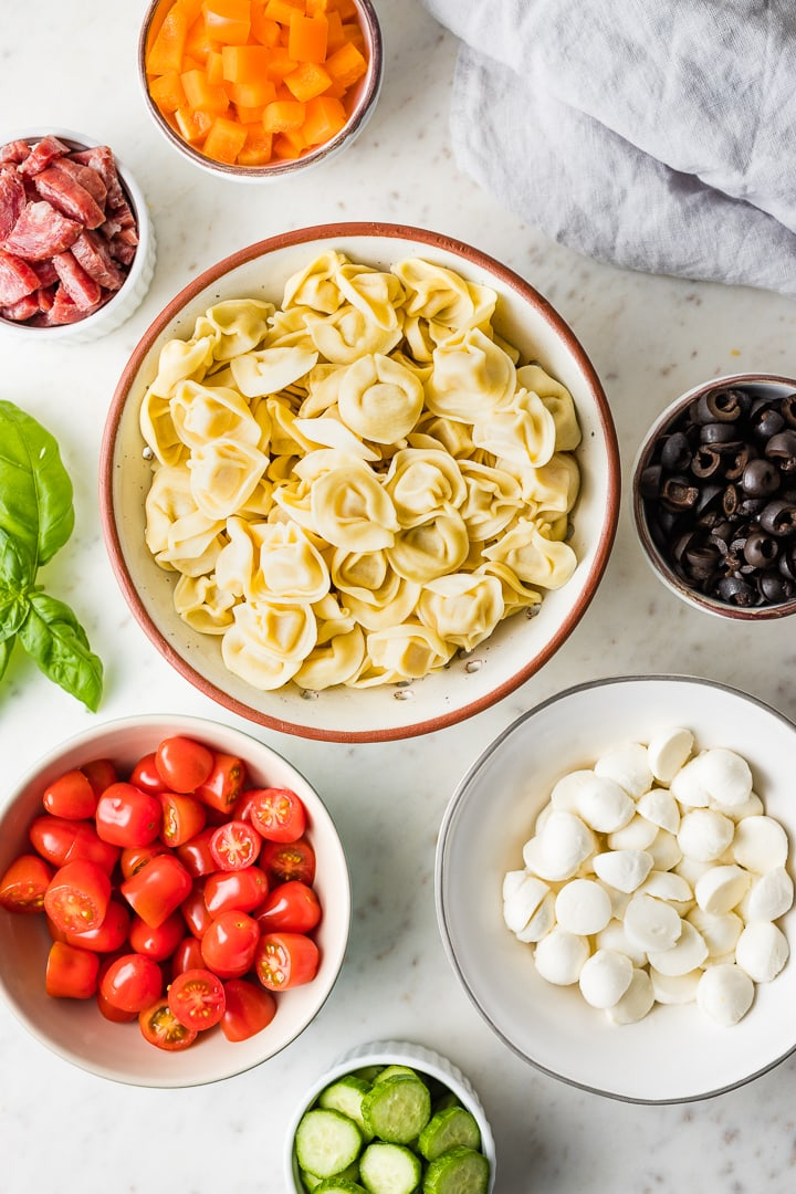Ingredients for tortellini pasta salad in bowls - tortellini, bell pepper, salami, tomatoes, cucumber, mozzarella, olives - arranged in a flat-lay.