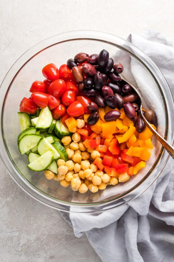 Prep bowl holding chickpeas, tomatoes, olives, pepper, and cucumber.