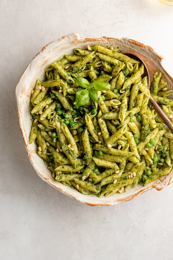 Large serving bowl filled with fresh pesto pasta with peas.