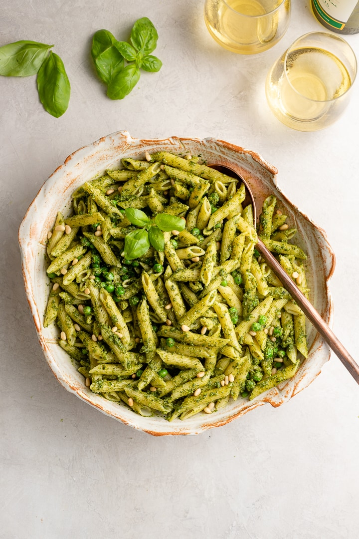 Large serving bowl filled with fresh pesto pasta with peas, surrounded by fresh basil leaves and glasses of white wine.