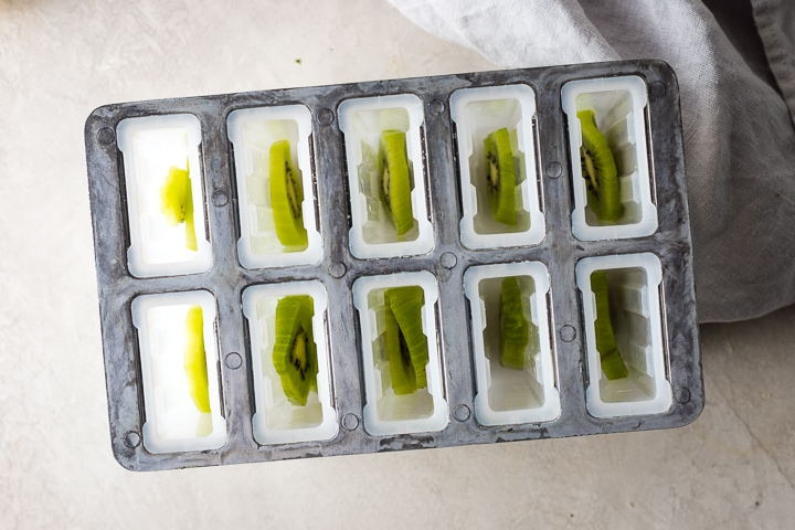 Popsicle molds with kiwi slices inside.