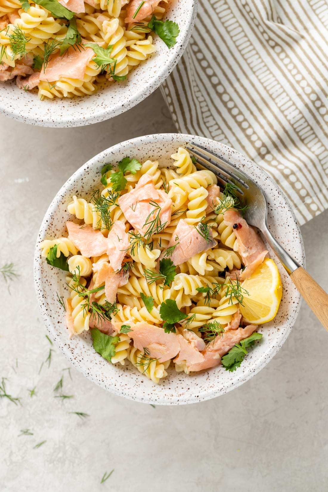 White bowl filled with a serving of Creamy Smoked Salmon Pasta with a lemon wedge.