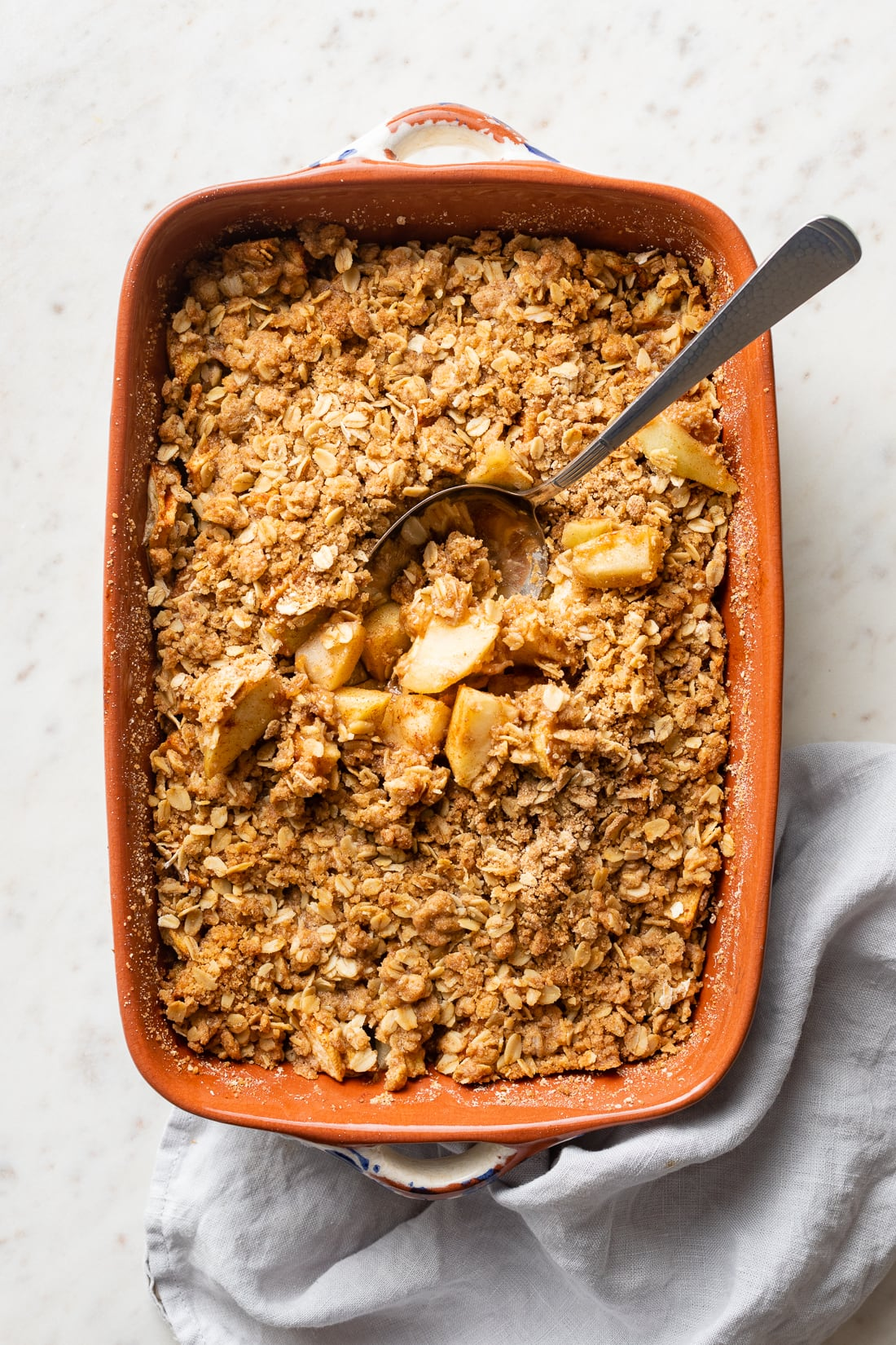 Baked pan of old fashioned apple crisp, with a serving spoon ready to dive in.