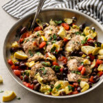 Skillet filled with Greek chicken with olives, tomatoes, and artichokes.