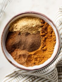 Cinnamon, ginger, nutmeg, cloves, and allspice in a small white bowl.