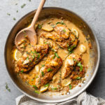 Creamy garlic chicken in a skillet with fresh herbs.