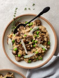 A bowl of mushroom risotto made in the Instant Pot with peas, Parmesan, and a garnish of fresh thyme.