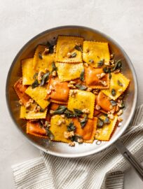 Skillet filled with pumpkin ravioli, sage brown butter sauce, crisped sage leaves, and walnuts.
