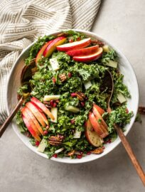 A large bowl of salad with kale, apples, Pecorino cheese, pomegranate seeds, and glazed pecans.
