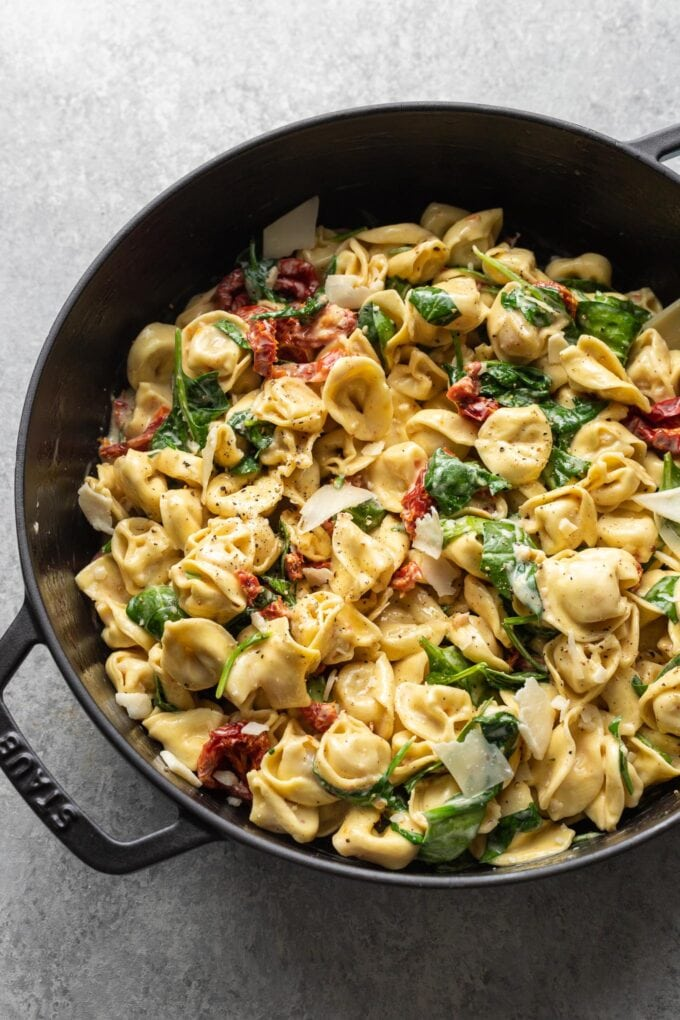 Cast iron skillet holding creamy Tuscan tortellini with spinach, sun-dried tomatoes, and shaved Parmesan.