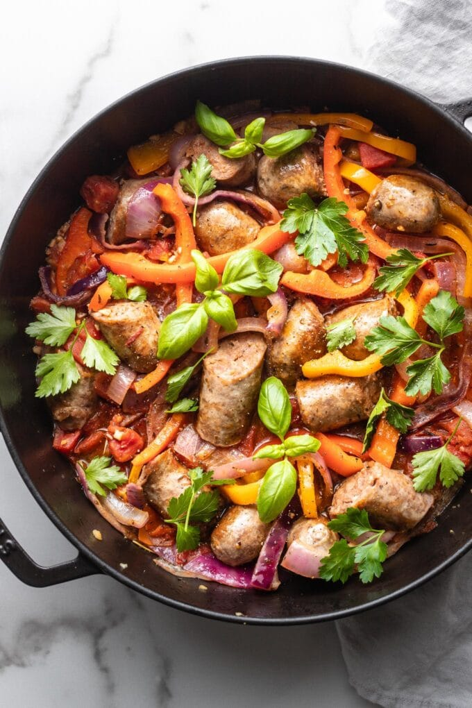 A skillet filled with Italian sausage, peppers, and onions, garnished with herbs and ready to serve.