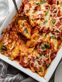 A large baking dish filled with baked stuffed shells filled with ricotta and spinach.