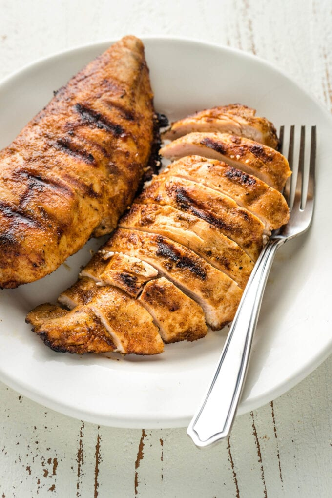 Slices of grilled chicken with dark grill marks on a plate with a fork.
