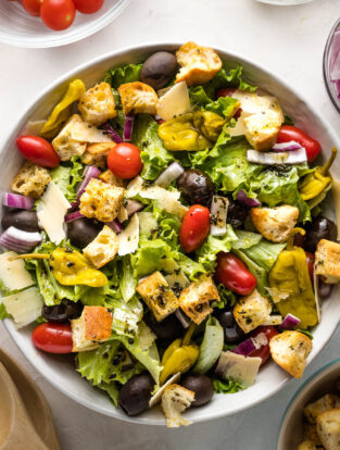 Large bowl of Italian salad with romaine, tomatoes, peppers, olives, and croutons.