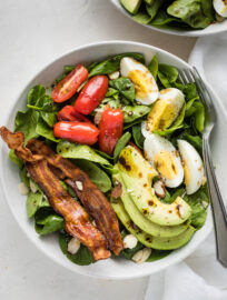 Spinach salad with bacon, hard boiled eggs, avocado, tomatoes, and a vinaigrette dressing.
