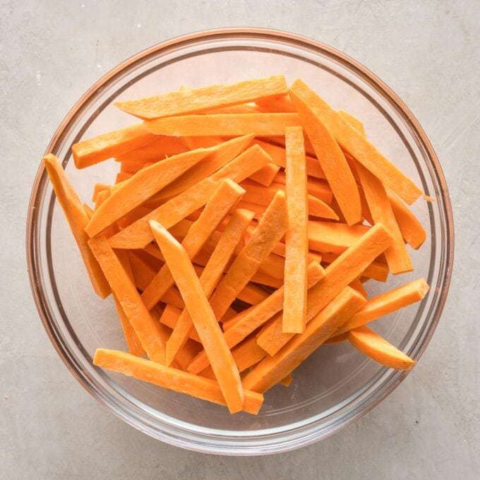Three sweet potatoes cut into french fries, in a clear glass prep bowl.
