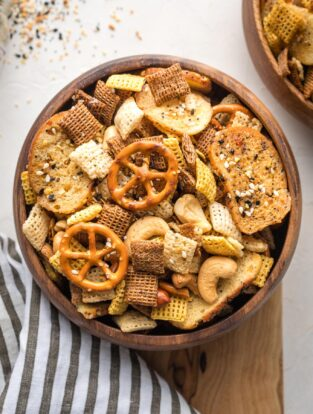 Small wooden snack bowl filled with everything bagel Chex mix.