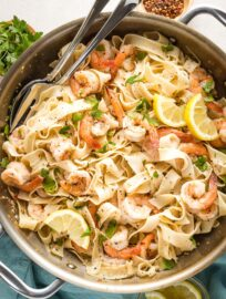 Large skillet filled with lemon pepper shrimp and pasta, ready to serve.