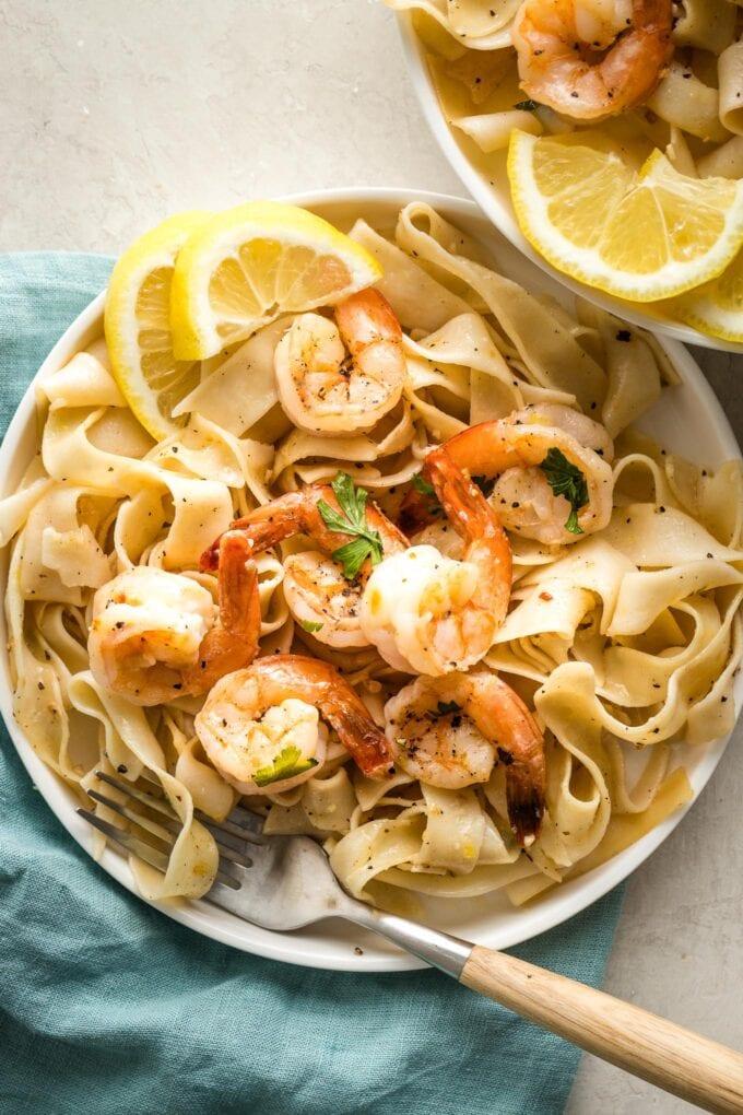 Small white plates with lemon pepper shrimp, pappardelle, and lemon slices for garnish.