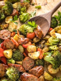 Close-up of spoon scooping up roasted chicken sausage and veggies.