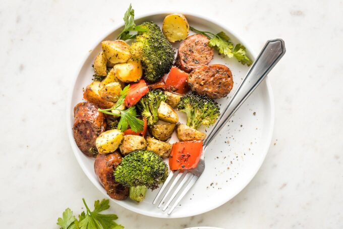 White plate with a serving of chicken sausage, broccoli, pepper, and potatoes.