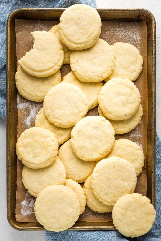 Weathered baking sheet with a batch of cookies arranged on top.