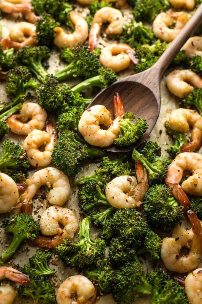 Wooden spoon serving honey garlic shrimp and broccoli off a pan.