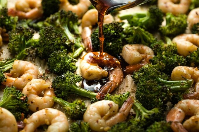 Honey garlic sauce being poured onto cooked shrimp.