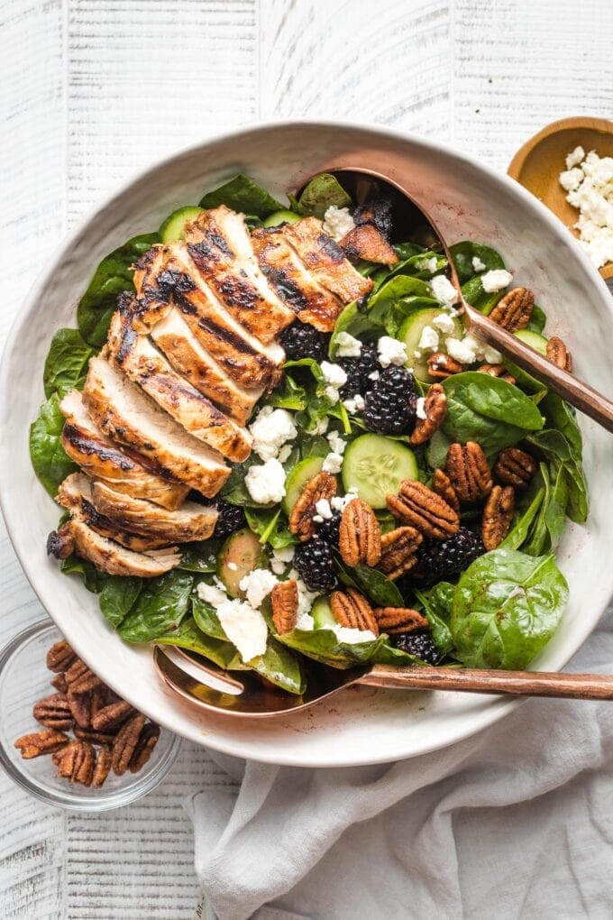 Large salad with spinach, blackberries, cucumber, and grilled chicken, in a white bowl ready to serve.