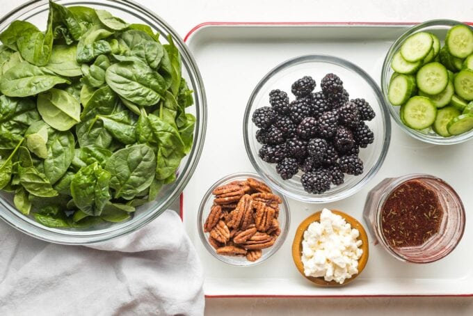 Prep bowls filled with baby spinach, washed blackberries, sliced cucumbers, pecans, crumbled feta, and a jar of dressing.
