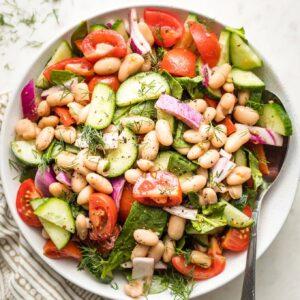 White bowl holding white bean cucumber tomato salad.