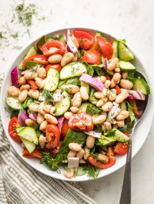 White bowl holding white bean cucumber tomato salad.
