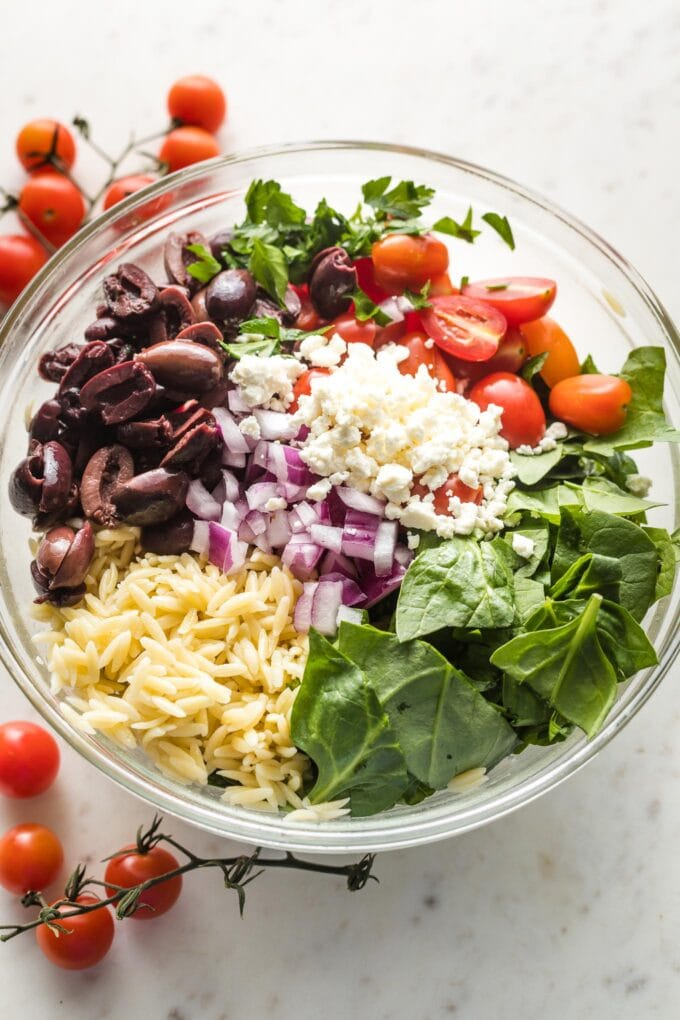 Prep bowl containing cooked orzo, halved cherry tomatoes, Kalamata olives, chopped baby spinach, crumbled feta, and a bit of diced red onion.