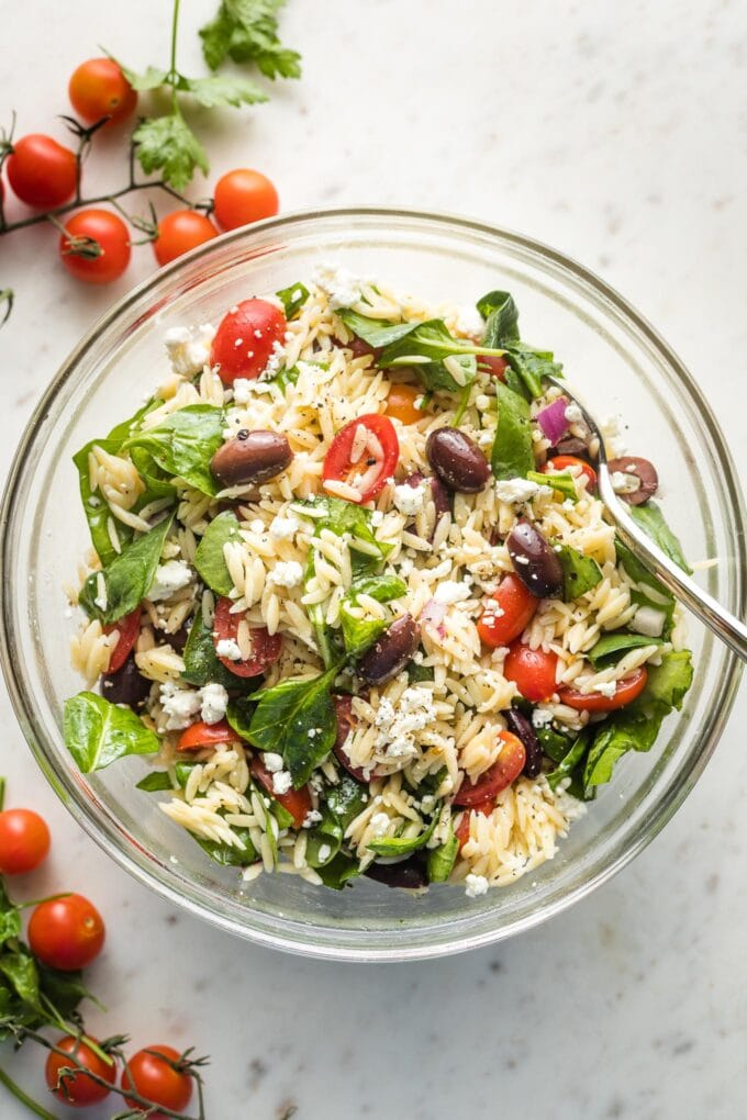 Clear bowl containing a Mediterranean orzo salad, ready to serve.
