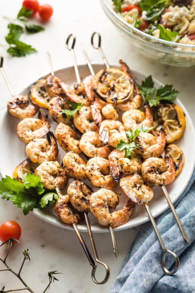 Plate holding grilled Greek shrimp on skewers.