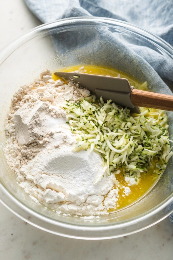 Prep bowl with egg mixture, flour, and grated zucchini.
