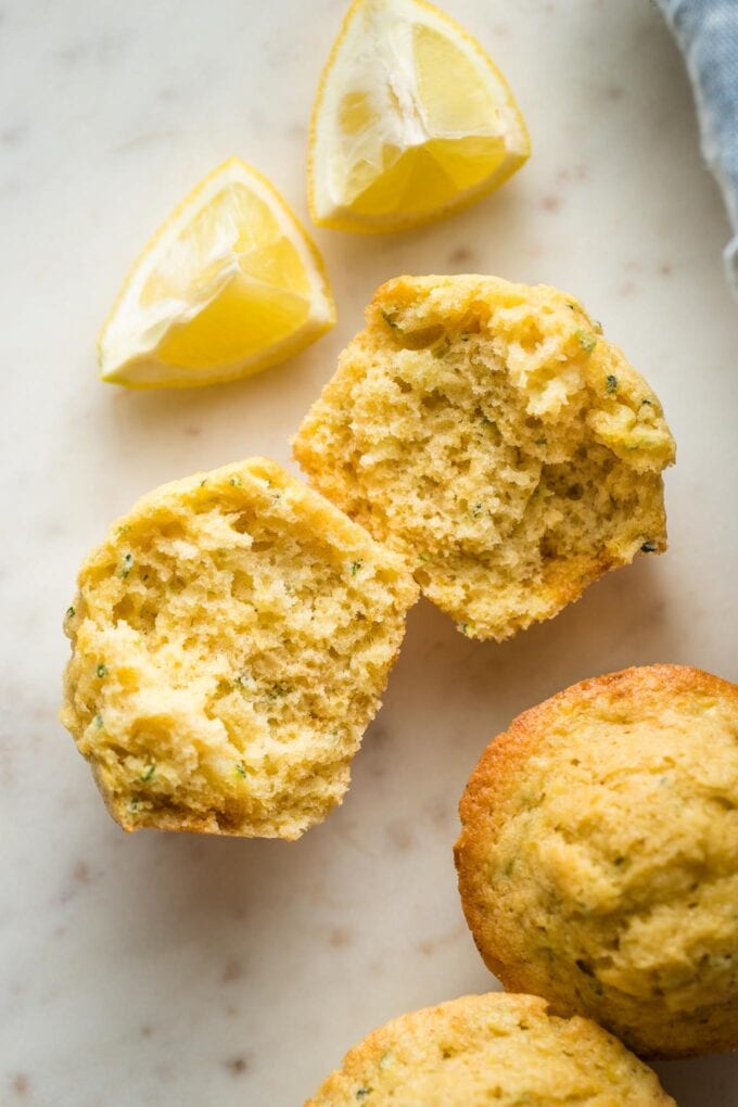 Close up of a lemon zucchini muffin split open to reveal the moist crumb and tender texture.