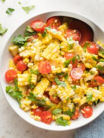 Roasted corn and tomato salad in a white bowl.