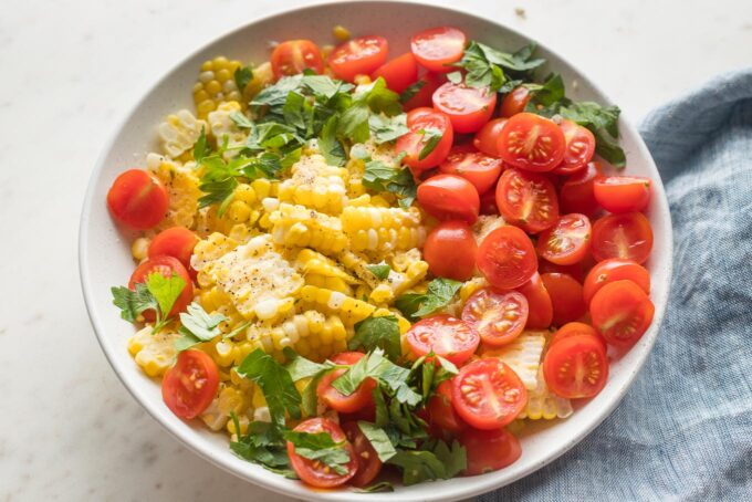Small bowl with corn, cherry tomatoes, and fresh chopped parsley.