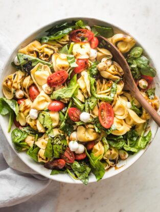 Large serving bowl full of tortellini Caprese salad with fresh mozzarella and spinach.