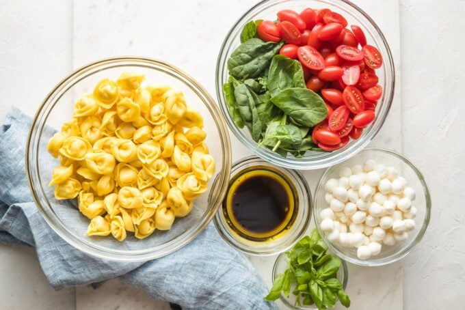 Prep bowls holding cheese tortellini, cherry tomatoes, baby spinach, mozzarella, fresh basil, and ingredients for a simple balsamic dressing.