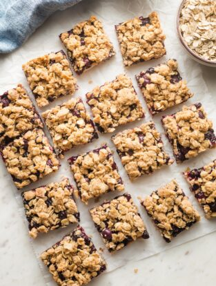 Squares of blueberry oatmeal bars arranged on parchment paper.