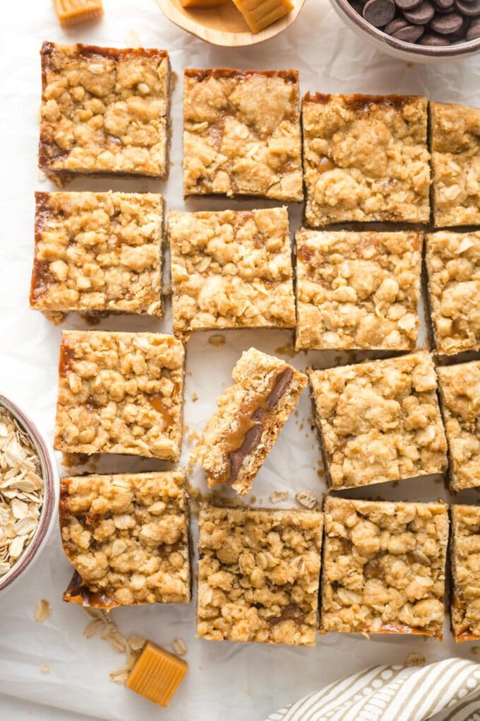 Just-cut squares of carmelita bars, laid out on white parchment paper.